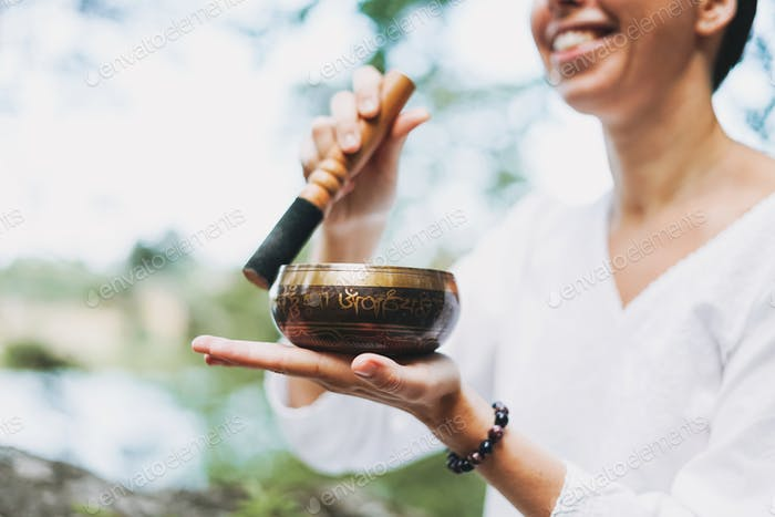 Young smiling woman playing on brass Tibetan singing bowl outdoor