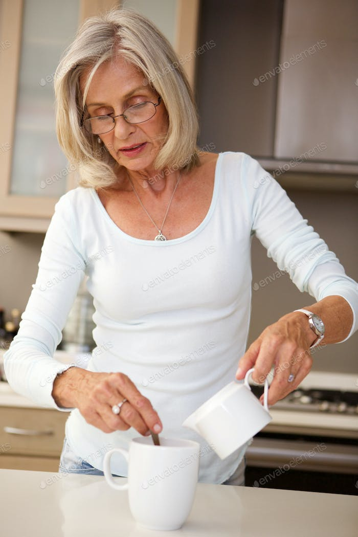 older woman pouring milk into coffee at home