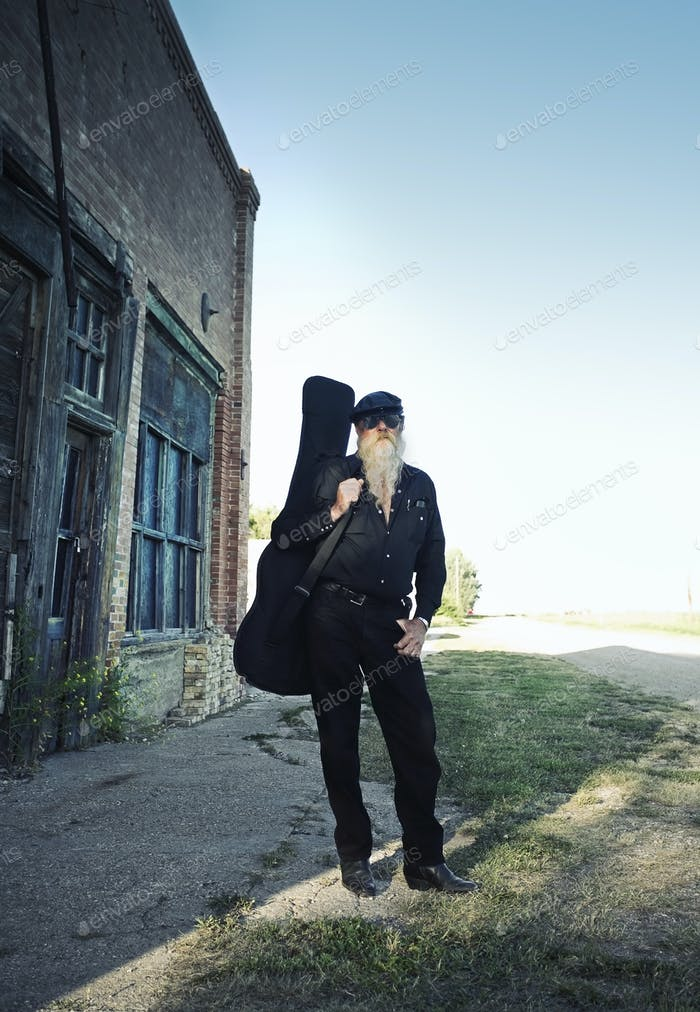 A man carrying a guitar.