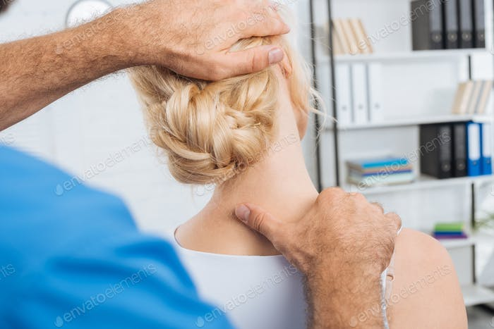 partial view of chiropractor stretching neck of woman during appointment in hospital