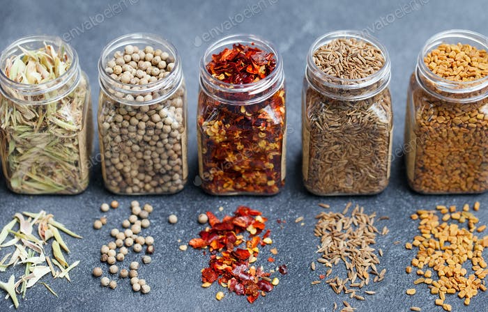 Assortments of Spices in Jars on Grey Stone Background.