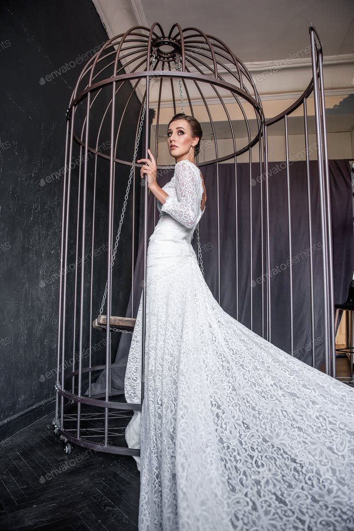 Fashion bride in an iron cage, unhappily looking out from behind bars. Life out of will.