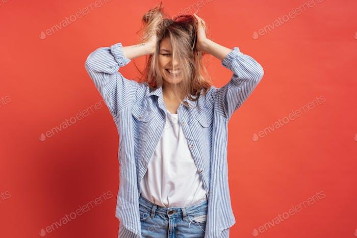 Lustig, niedlich Mädchen mit Spaß beim Spielen mit Haar isoliert auf einem roten Hintergrund