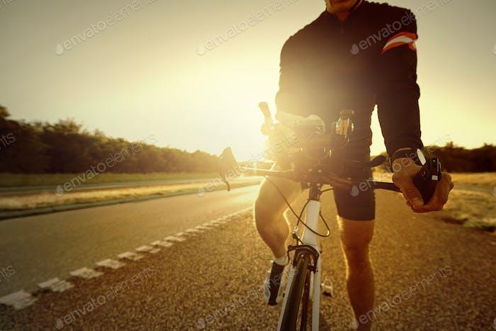 Велосипедный спортсмен, стоящий на пустом шоссе