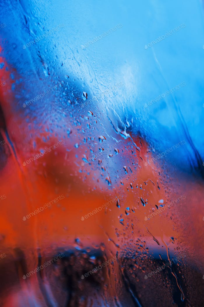 Water droplets on neon glass background. Red and blue colors