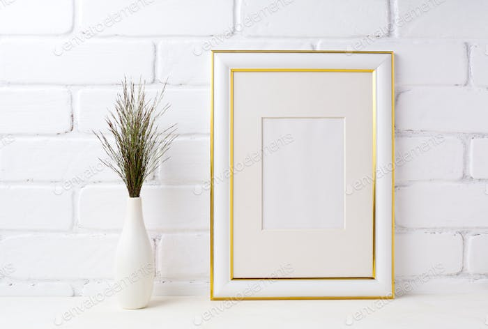 Gold decorated frame mockup with dark grass in vase near brick w