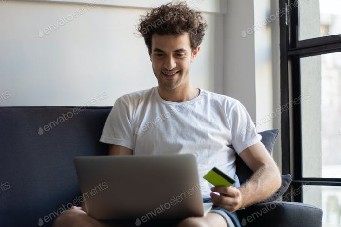 Man with laptop and credit card at home.