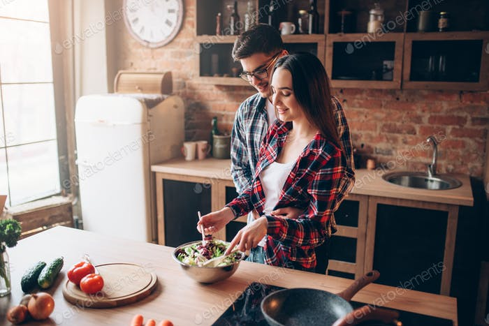 Love couple cooking on kitchen, salad preparation