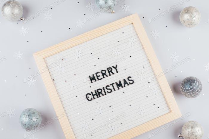 Weihnachtskugeln, graue und silberne Verzierungen Leuchtkasten mit Text Frohe Weihnachten. Flach legen