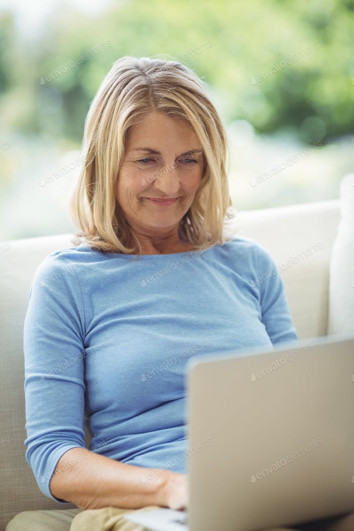 Senior woman using laptop in living room