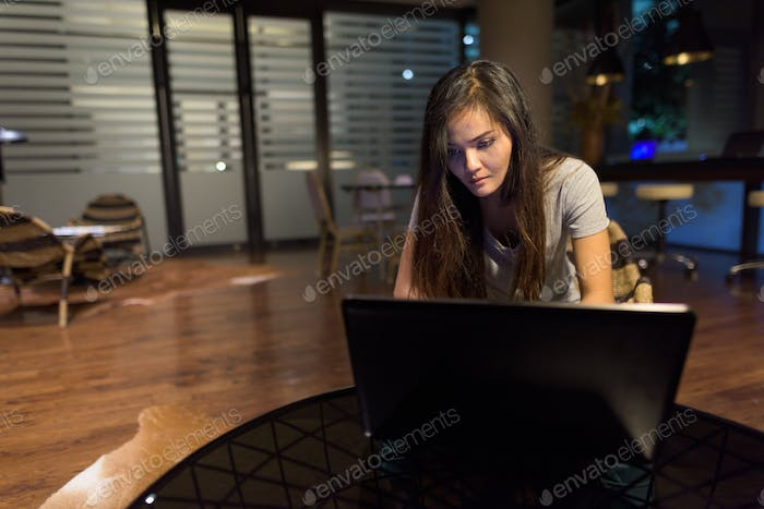 Young beautiful Asian woman using laptop in the living room