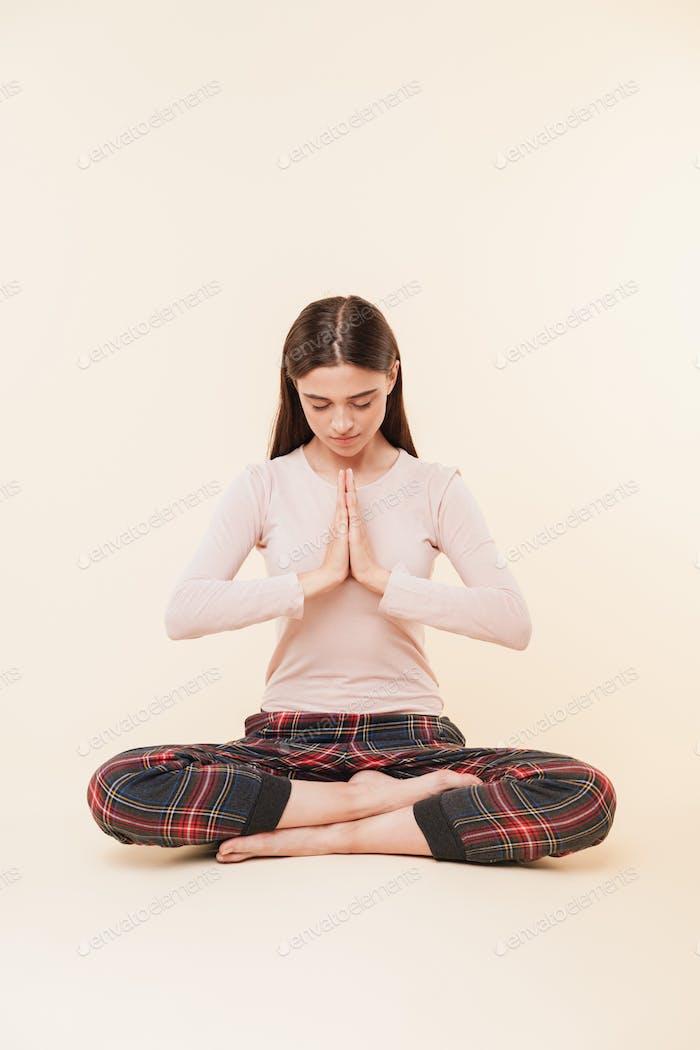 Patient young brunette girl meditating