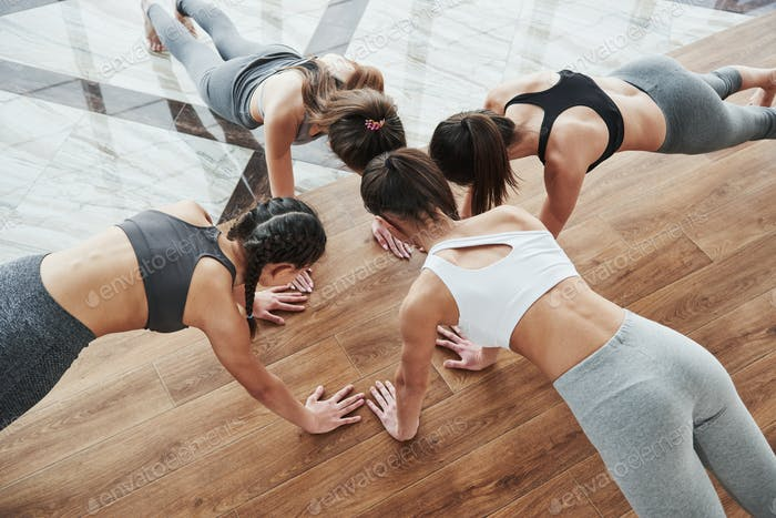 Young girls doing push ups together. Head near head pose on the wooden and tile floor