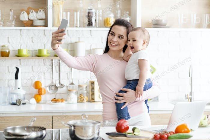 Millennial mother taking selfie on cellphone, smiling at camera