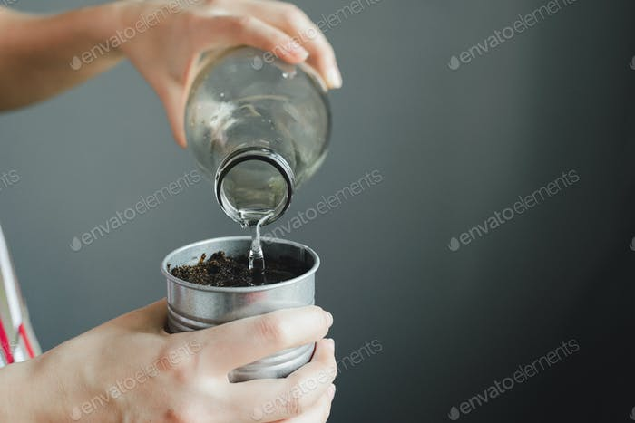 womans hand holding glass bottle and watering soil in metal pot for houseplant