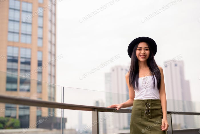 Happy young beautiful Asian tourist woman against view of the city