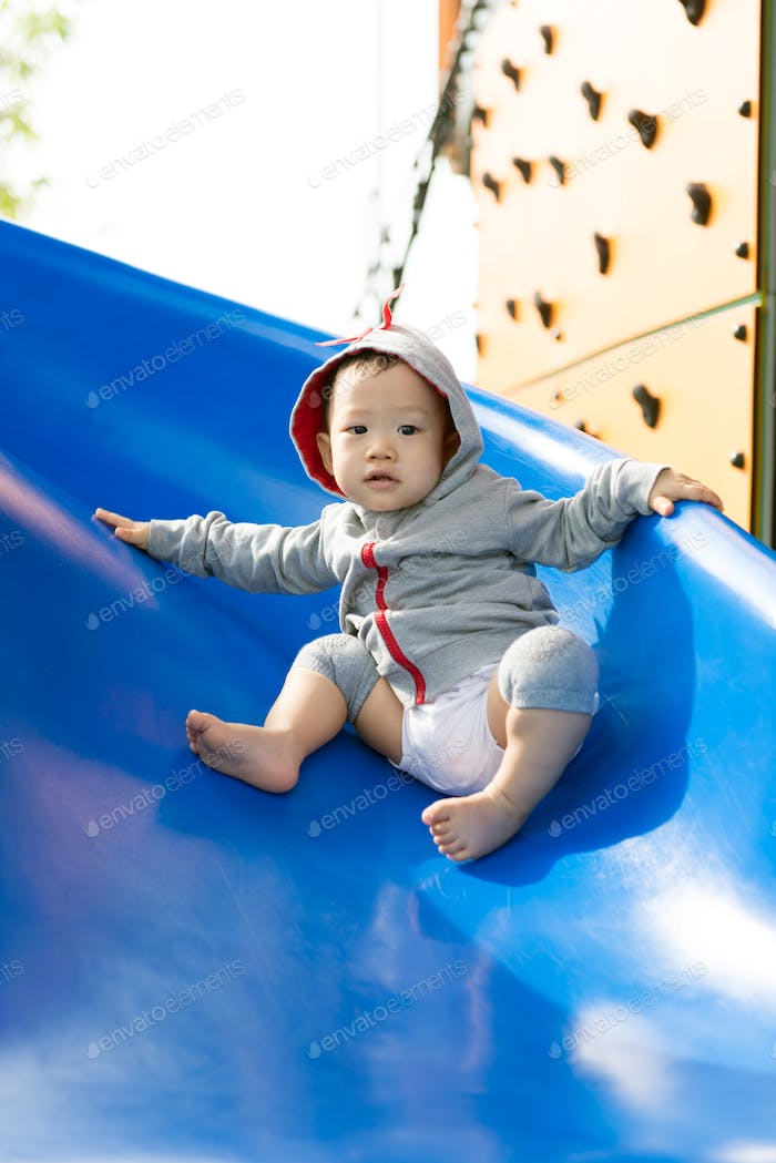 Small Asian baby boy playing slide