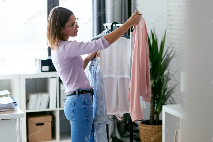 Beautiful young woman looking and choosing outfit at home wardrobe.
