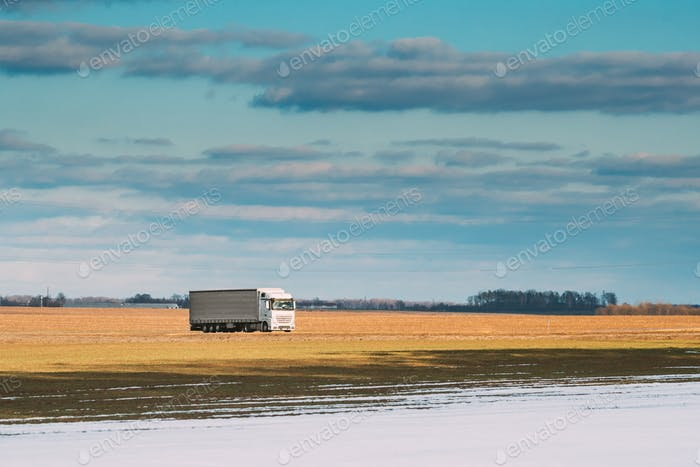 Truck Or Tractor Unit, Prime Mover, Traction Unit In Motion On Road Through Field
