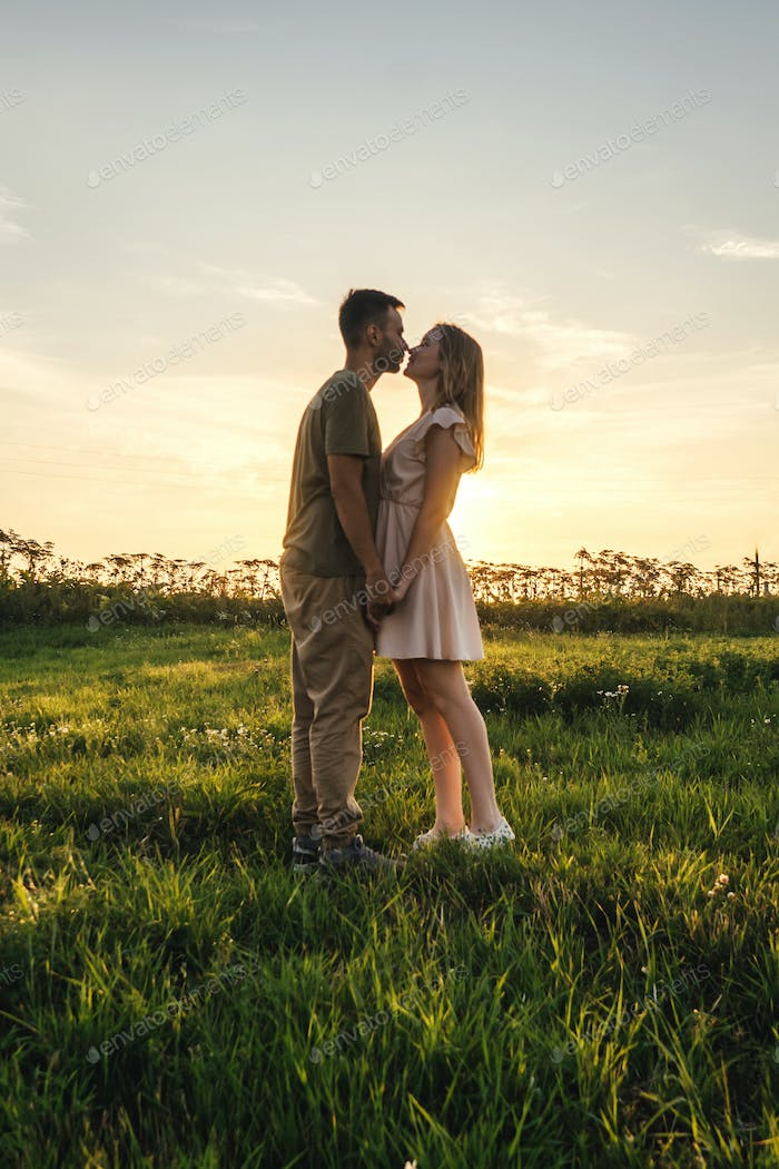 Loving couple in the field. Sunset.