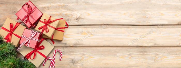 Geschenkboxen mit roten Bändern und Zuckerstangen auf Holzhintergrund, Banner, Kopierraum, Draufsicht