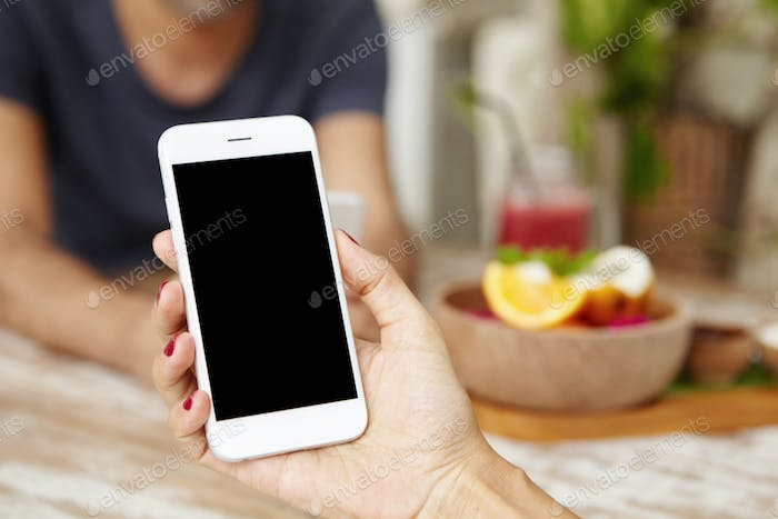 People, technology and lifestyle concept. Close up shot of female hand holding smart phone, browsing