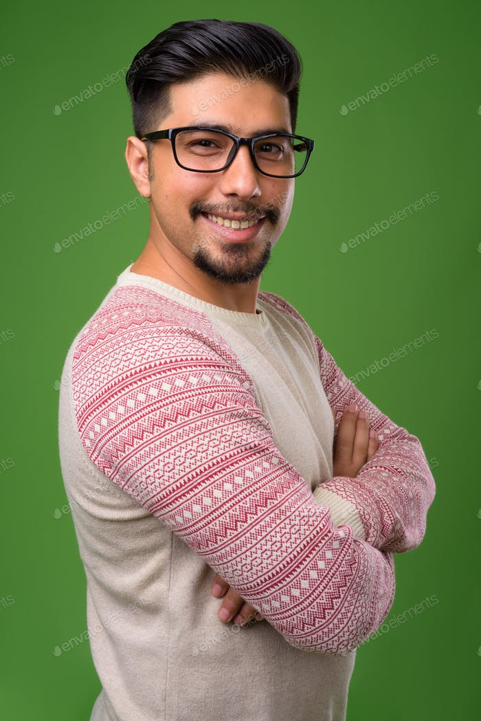 Young bearded Iranian man against green background