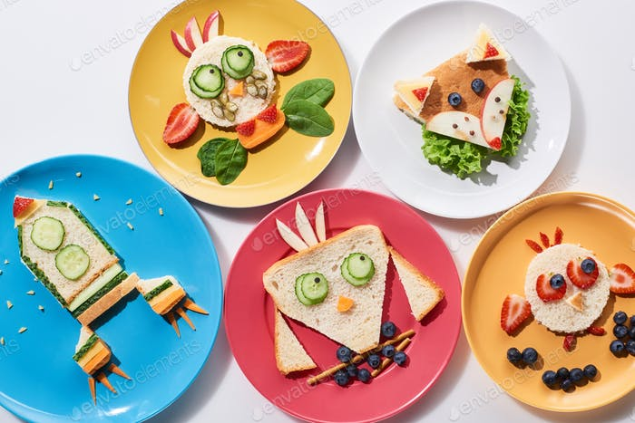 Plates With Fancy Animals And Rocket Made of Food For Childrens Breakfast on White Background