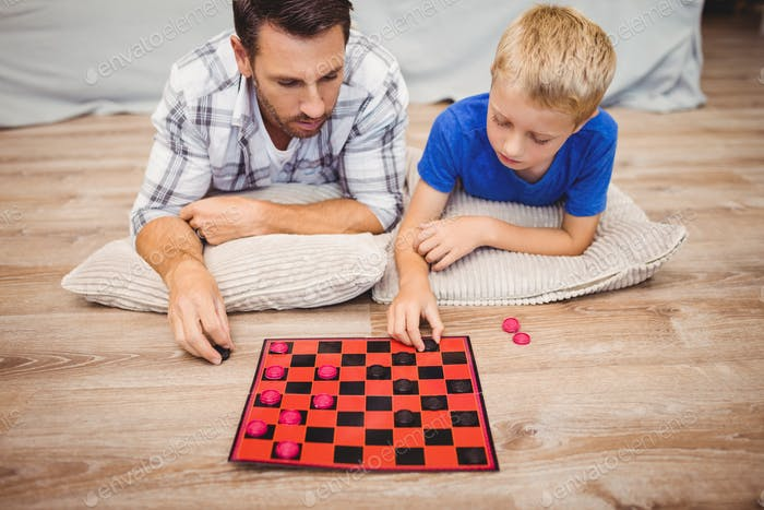 Father and son playing checker game while lying on hardwood floor at home
