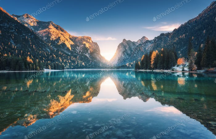 Lake in fog with reflection of mountains at sunrise in autumn