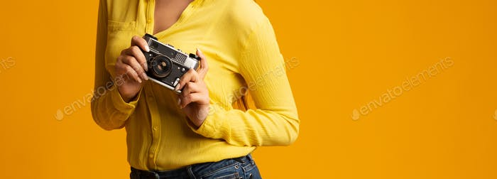 Unrecognizable millennial girl holding retro camera on yellow background, cropped