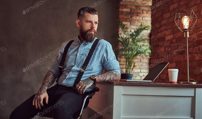 Thumbnail for Красивый татуированный хипстер в кабинете с интерьером лофта.
