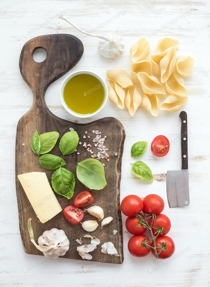 Ingredients for cooking pasta. Conchiglioni, basil leaves, cherry-tomatoes, Parmesan cheese