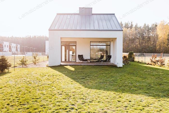 Moderne Gartenmöbel auf der Terrasse des stilvollen Vorstadthauses mit großem grünen Hof