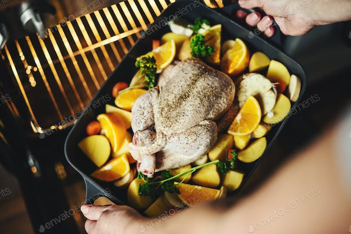 Woman cooking raw chicken with vegetables