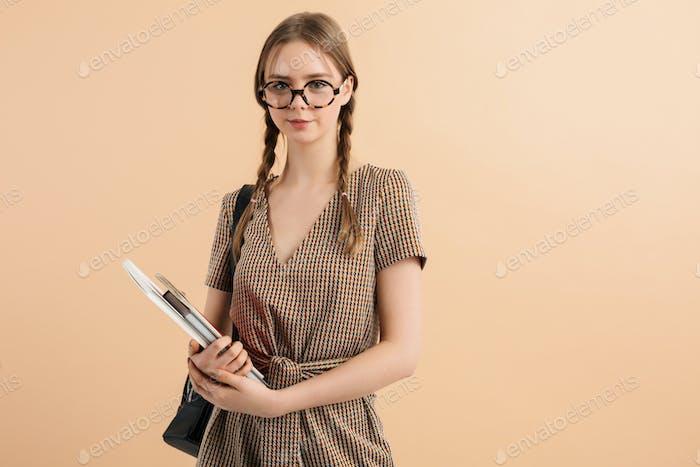 Smiling school girl with braids in tweed jumpsuit and eyeglasses dreamily looking in camera