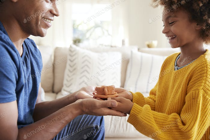 Close up of pre-teen girl presenting a handmade gift to her father, side view