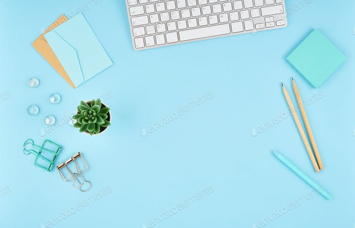 Blauer Büro-Desktop. Draufsicht des modernen hellen Tisches mit Bürobedarf, Tastatur