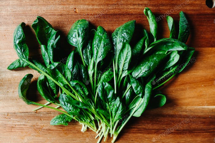 Top view of fresh spinach leaves on a wooden cutting board