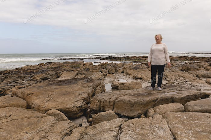Happy senior woman standing on the rock at beach with ocean in the background