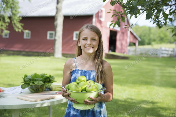 A young girl carrying a large bowl of crisp green skinned apples.