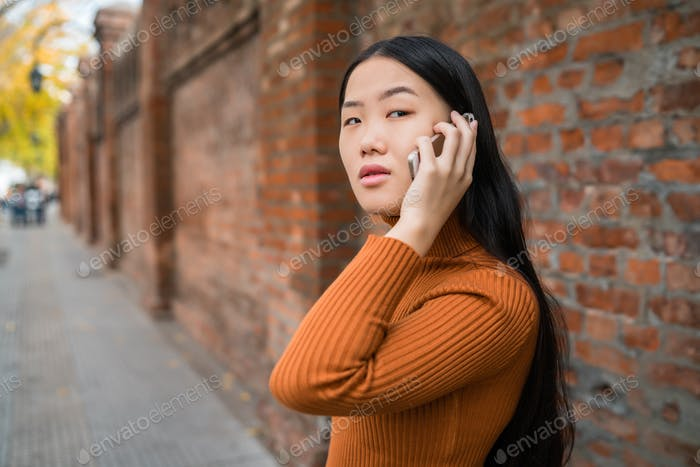Asian woman talking on the phone.