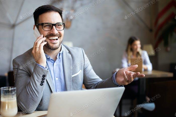 Porträt eines erfolgreichen Geschäftsmann sitzt im Café vor einem Laptop