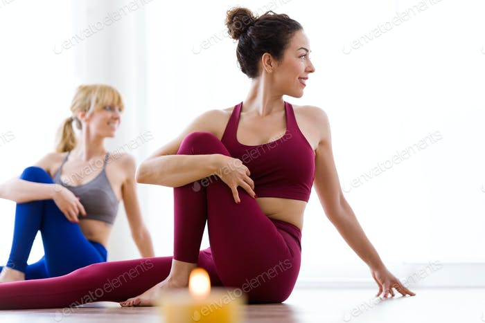 Two pretty young women practicing yoga at home. Marichyasana pos