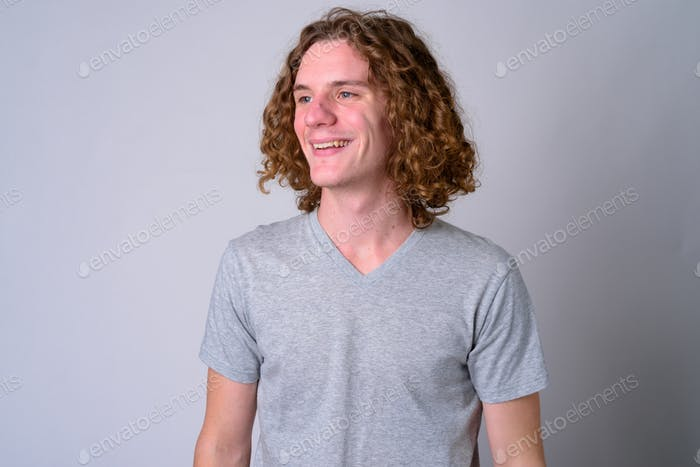 Face of happy young handsome man with curly hair thinking