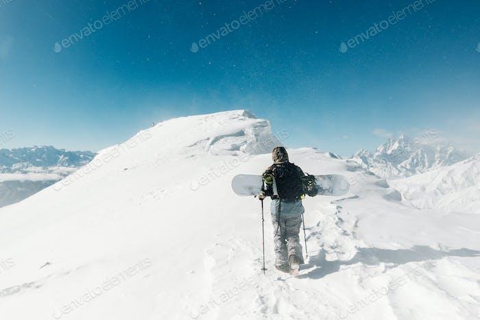 Sportler gehen mit Snowboard-Ausrüstung im Schneesturm