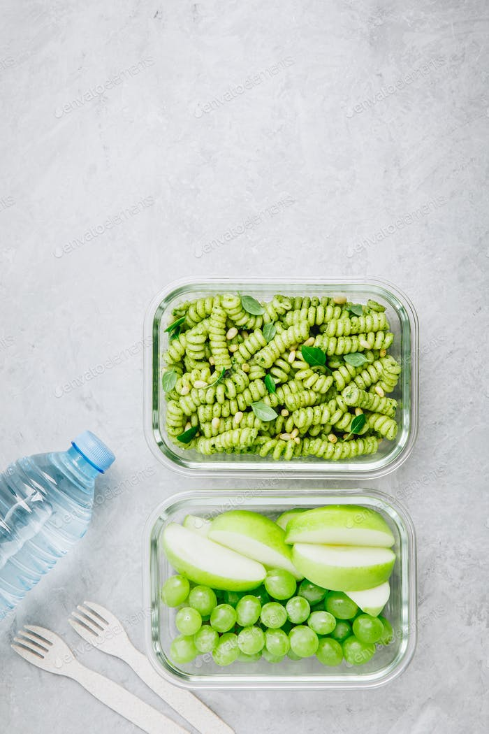 Vegetarian meal prep containers pesto pasta with basil and pine nuts. Apple and grape for dessert.