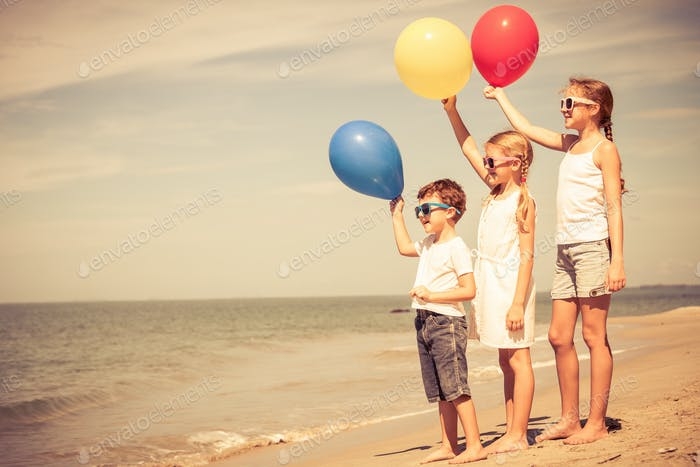 Three happy children with balloons  standing on the beach at the