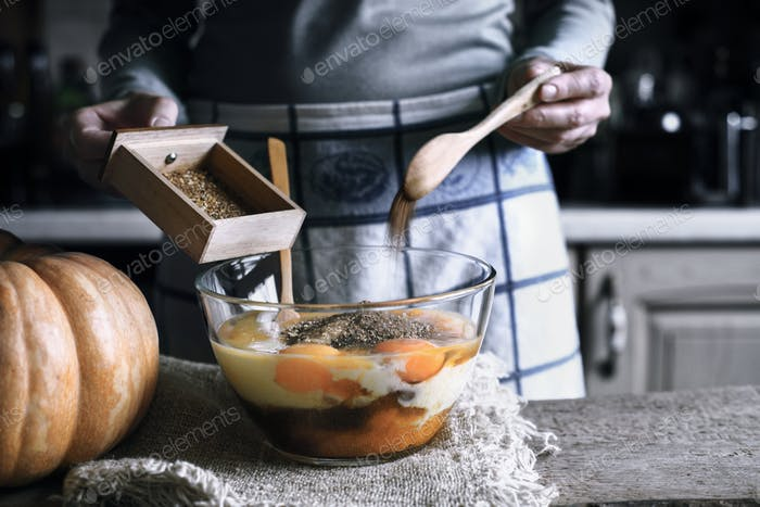 Adding spices in the glass bowl with in the dough for pumpkin dump cake