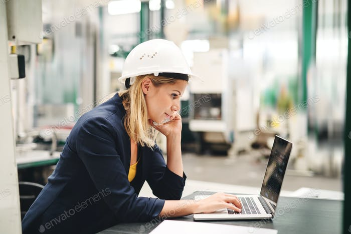 An industrial woman engineer in a factory using laptop and smartphone.